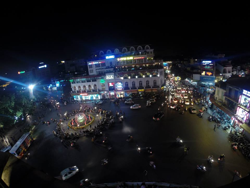 View from the 4th floor of a restaurant in Hanoi at night, the roundabout is lit up and there are people and scooters everywhere