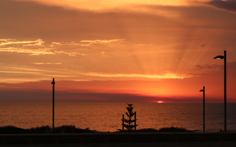 Pastel orange, pink, purple, and dark pink as the sun sinks over the ocean, beams of light shining out