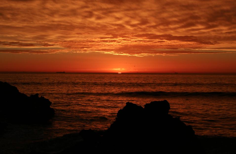 dark orange sky, sun about to sink below the horizon