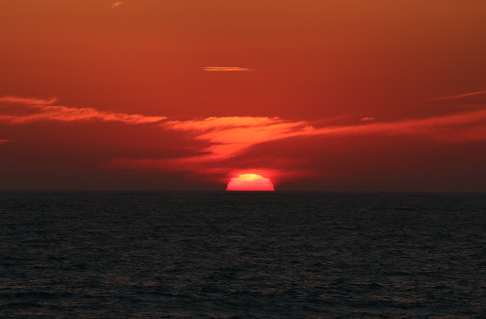 Bright red sun, the whole sky lit up dark red over the ocean