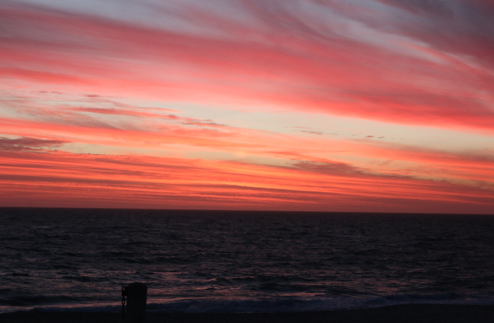 streaks of pink, blue, yellow and red across the blue sky over the ocean