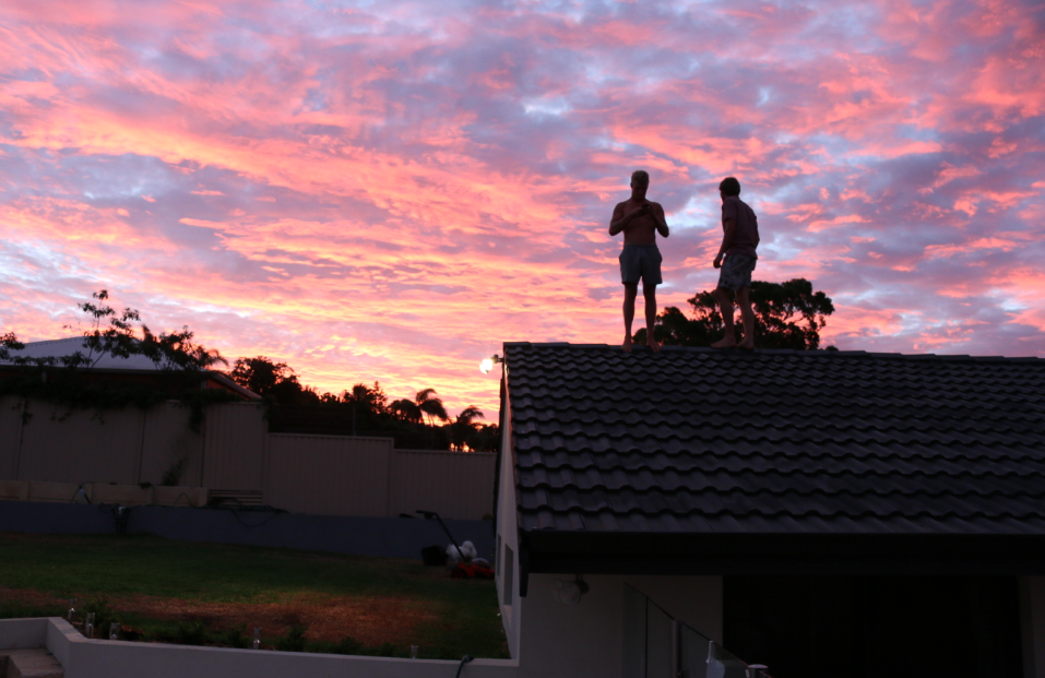 the shadows of two males standing on the roof, purple pink and blue sky, dotted with clouds