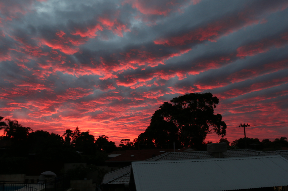 sunset over the roof of the house, grey and pink clouds lined up across the sky