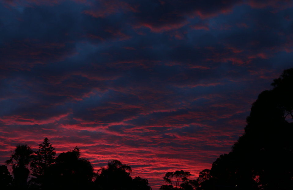 Deep red coloured clouds, dark skies directly above