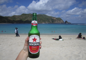 Holding up a large bintang on the beach with the ocean in the background