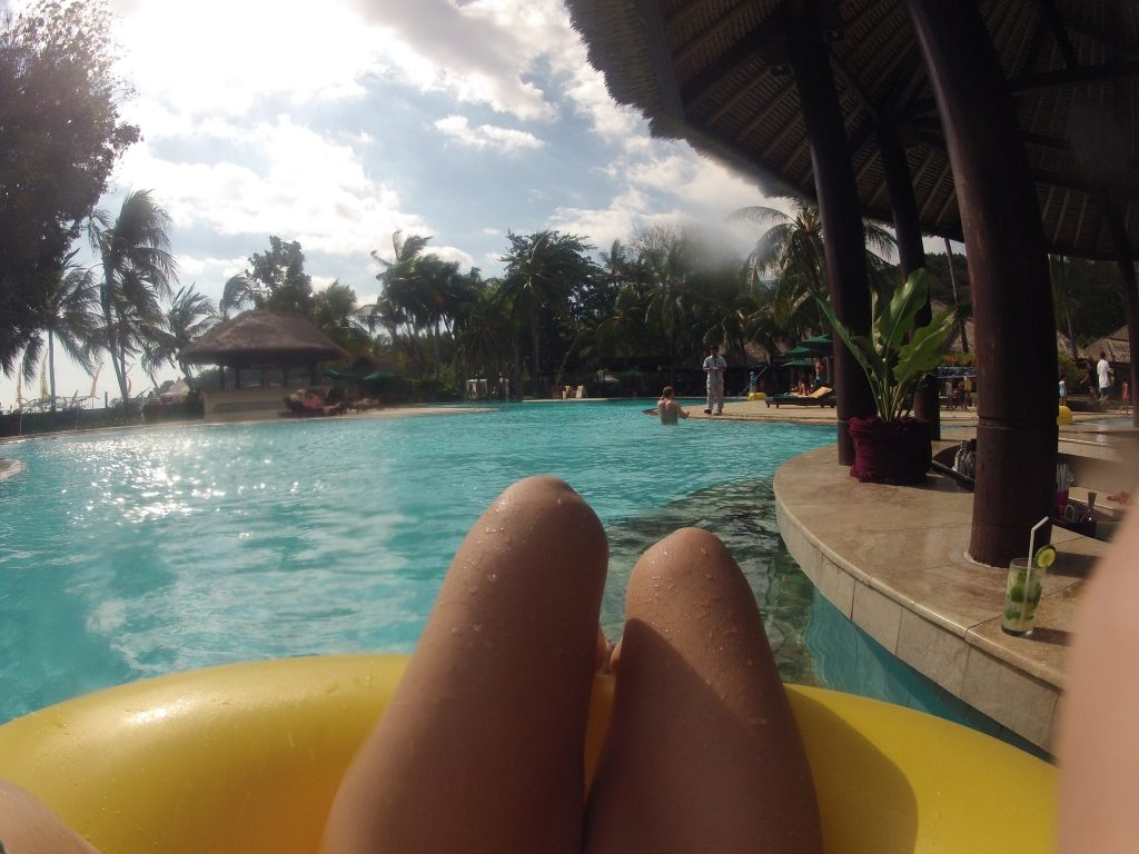 Picture of Tegans legs in a flotation ring in the pool, palm trees in the background, pool bar to the right