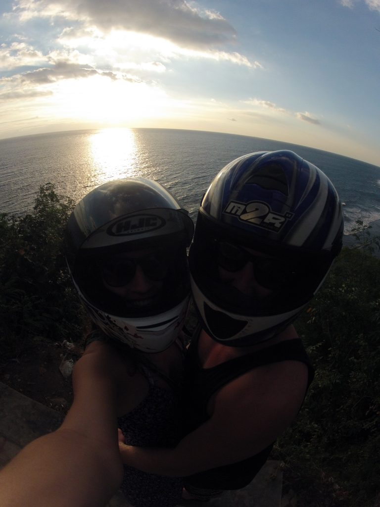 Tegan and dan with motorbike helmets on and the sun over the ocean behind them