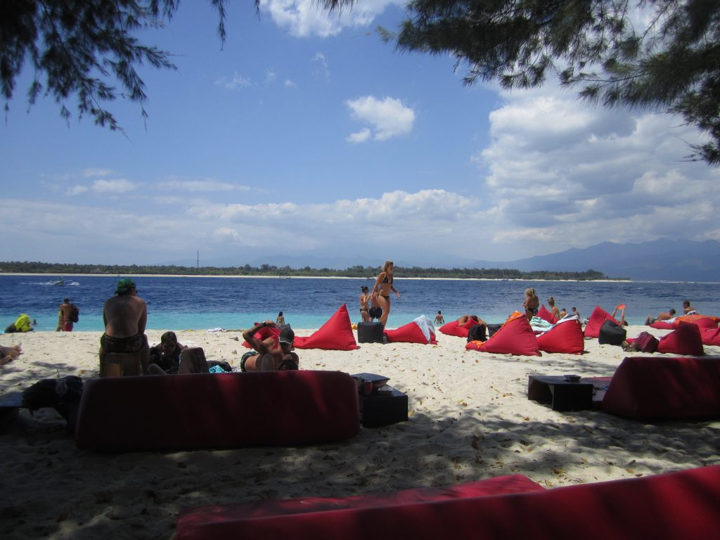 Bean bags on the sand at the beach at gili t. A few clouds but a beautiful day