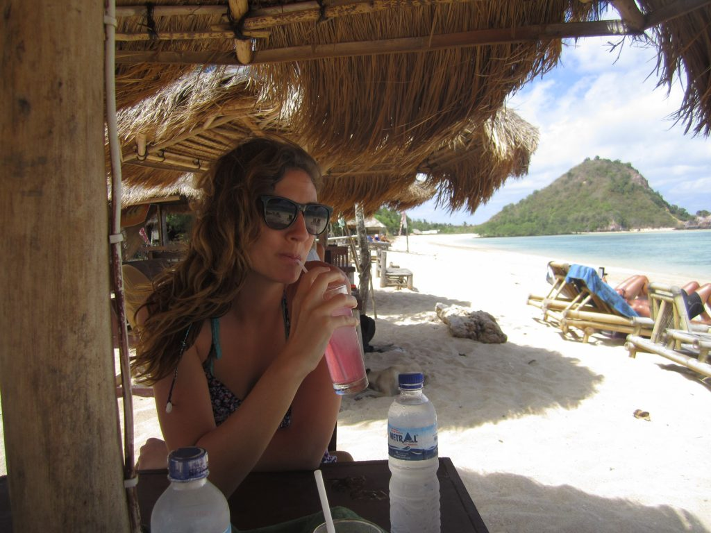 Tegan drinking a pink cocktail on the beach, under the thatched umbrella