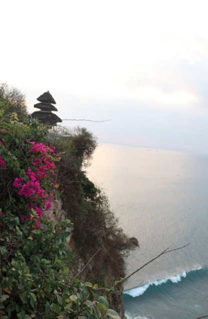 View of a mini balinese pagoda on the cliff top at Uluwatu temple, bright pink flowers