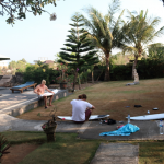 Boys, waxing up their surfboards on the lawn in Uluwatu