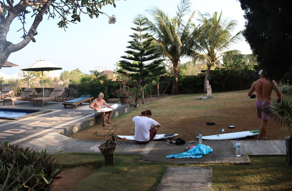Boys, waxing up their surfboards on the lawn in Uluwatu