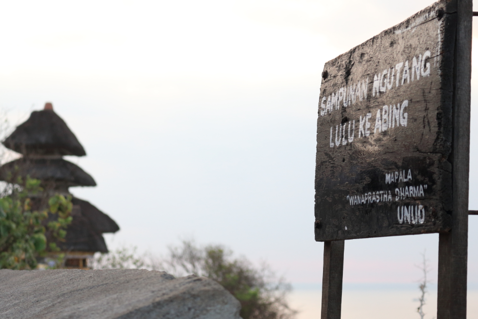 Sign for the uluwatu temple overlooking the ocean