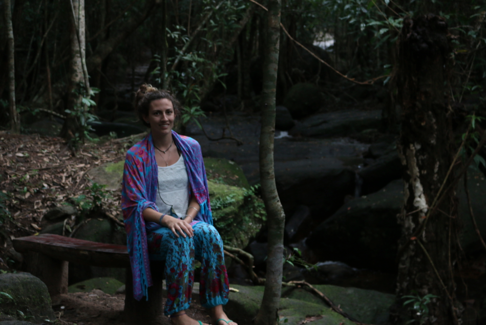 Tegan sitting on a seat in the forest with moss coloured rocks around her