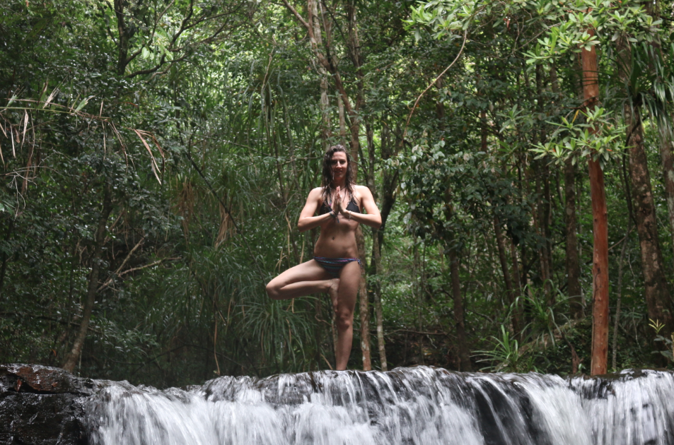 Tegan standing on top of the waterfall in tree pose, surrounded by lush green trees