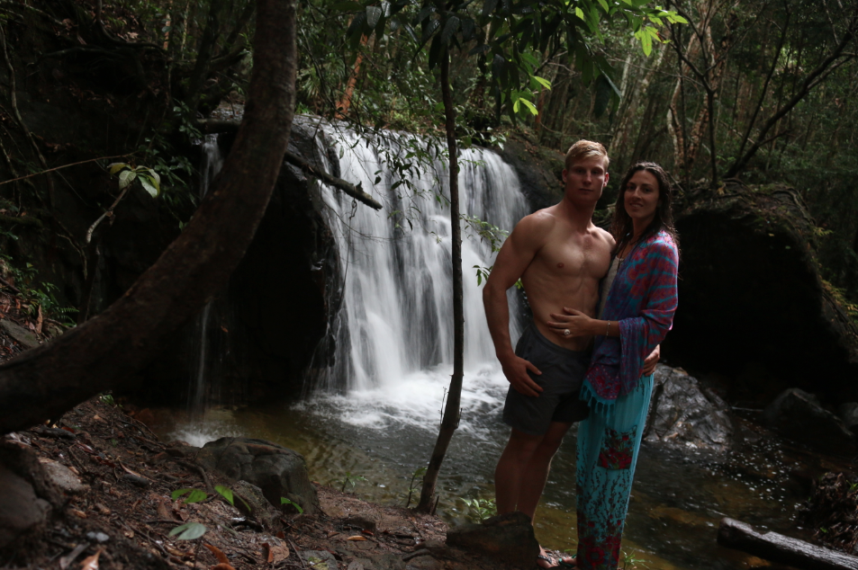 Tegan and Dan standing in front of the waterfall at Phu Quoc, amongst the trees