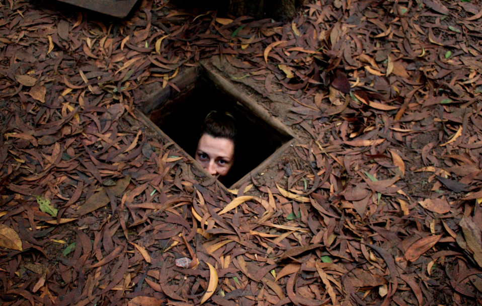 Tegan poking her head out of a small opening at the tunnels, surrounded by dirt and leaves