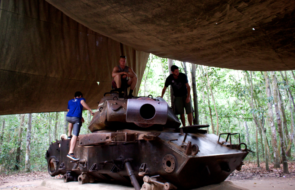 Dan sitting on an army tank at the chu chi tunnels