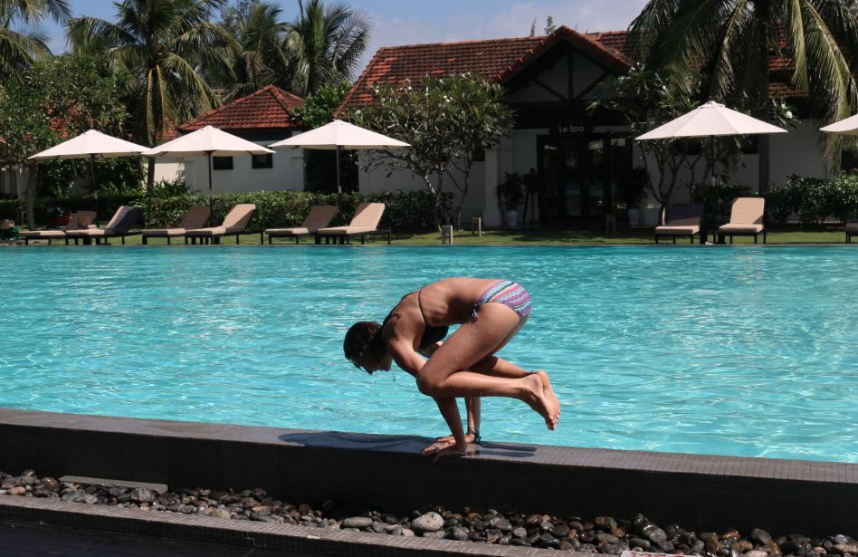 Tegan in her bikini on the pool edge doing the yoga 'crow pose'
