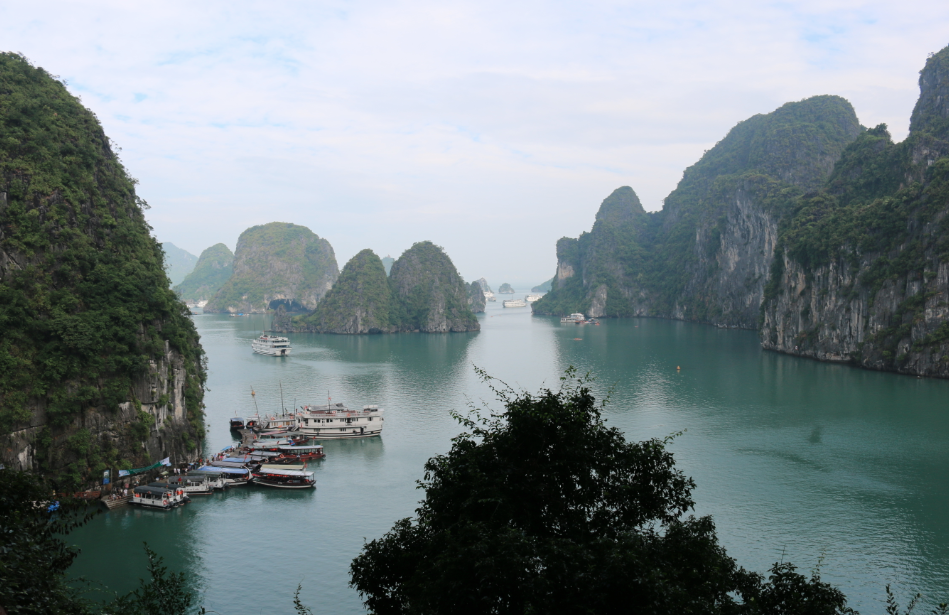 A view of Ha Long Bay from a lookout a top a limestone mountain, overlookng the turquoise bay, a few boats and more limestone mountains
