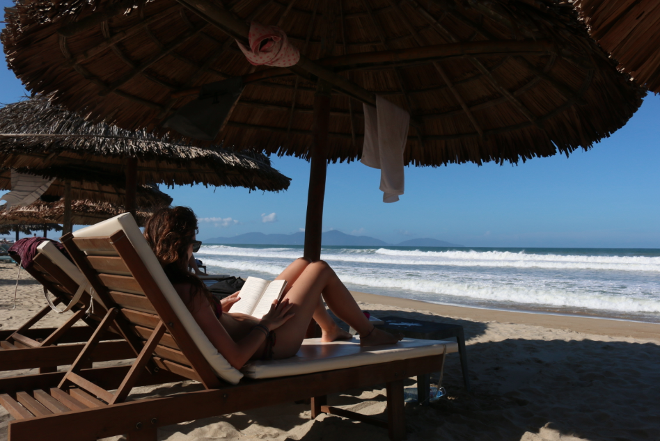 Tegan reading a book on a sun bed under a thatched roof of a hut on the beach, swell rolling through in the background, towel hanging from the roof