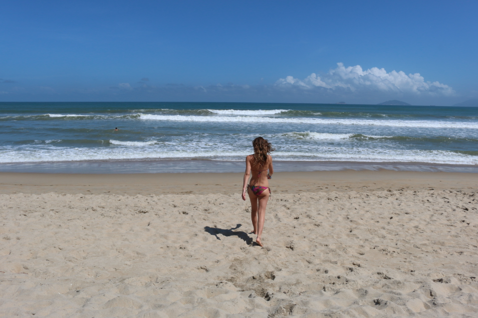 Tegan walking to the surf in her bikini, bright blue sky, welcoming ocean, swell rolling through and no one else around