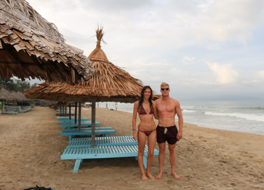 Tegan and Dan standing on the beach in front of the thatched huts, blue sunbeds under them but no tourists as it has just rainied. Both Tegan and Dan in their swimming costumes soaking up the rain