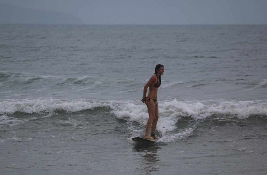 Tegan picking her bikini wedgie while surfing a longboard at Hoi An
