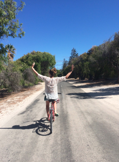 Tegan riding a bike with her arms outstretched, sand on either side of the road as well as trees