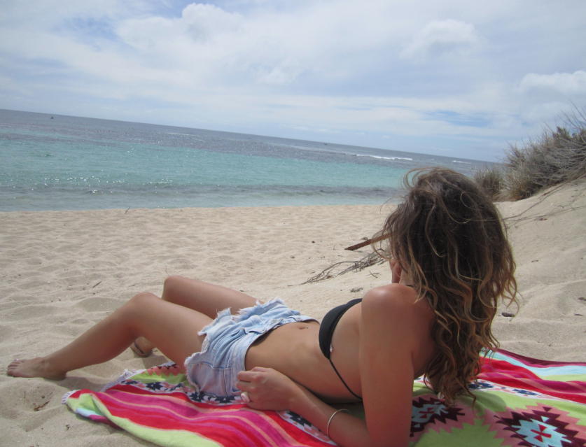 Tegan laying on the beach looking out to the surf