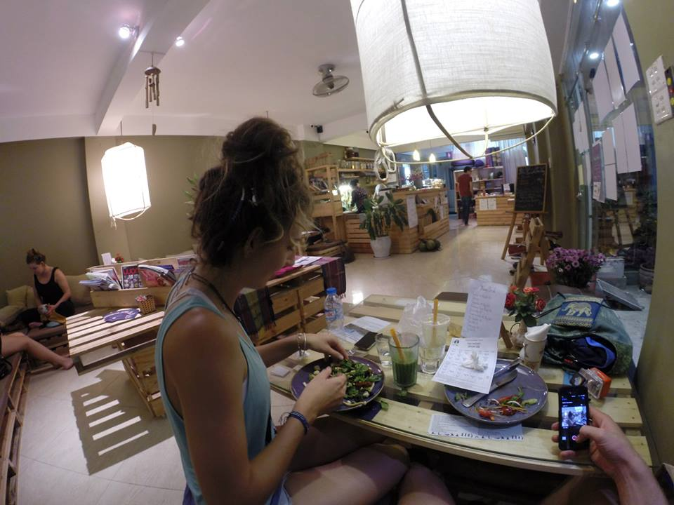 Tegan eating a veggie pizza in a yoga studio cafe after class, wooden pallet tables and seats with cushions on them