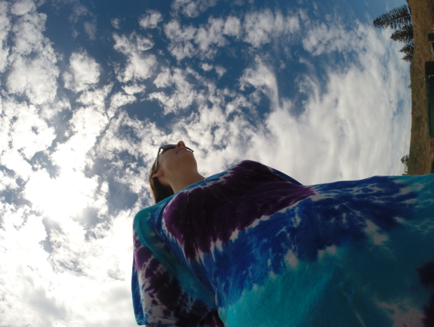Picture looking up towards the sky, tegan wearing tie dye with blue skies and white clouds