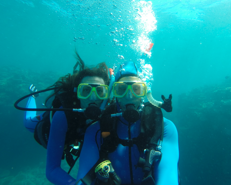 Selfie underwater, blue lycra stinger suits, bubbleson their way to the surface