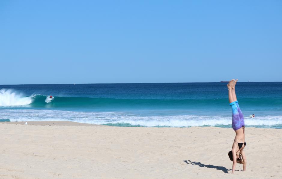 Tegan looking at the ocean, wave breaking in the left hand corner, blue skies and blue seas