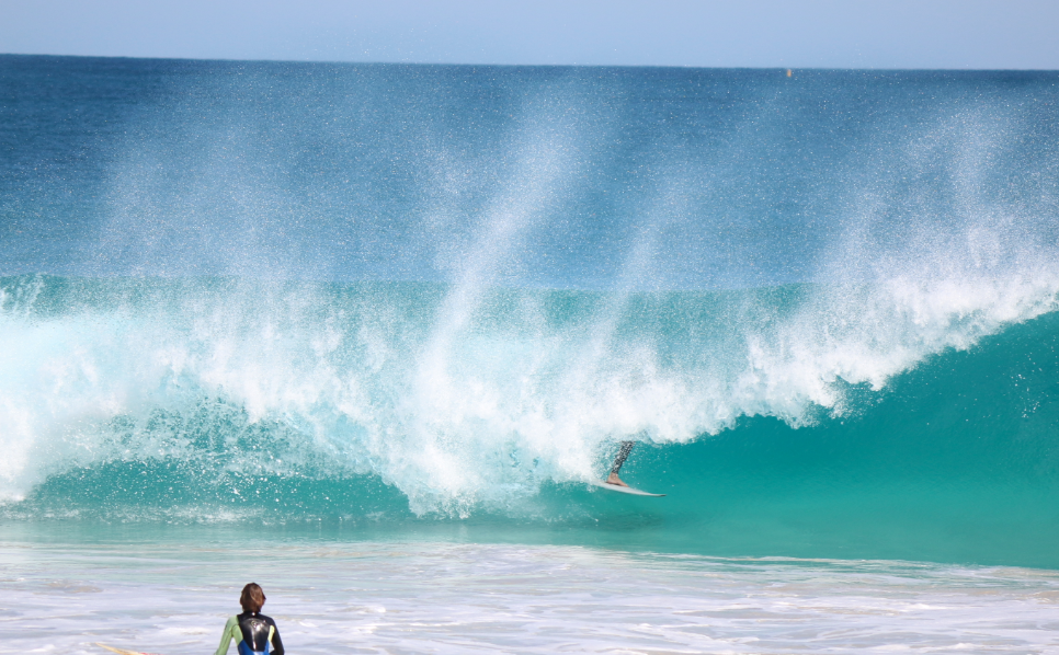 blue ocean, turquoise clear face offshore wind blowing the white wash behind the wave, Dan covered up, in the barrel
