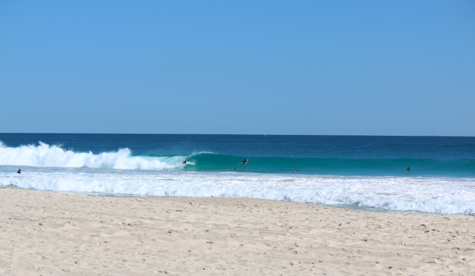 Turquoise wave, 2 surfers paddling out, clear blue skies