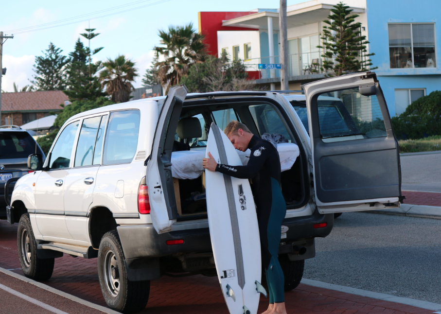 Dan waxing his board in his wetsuit out the back of our landcruiser with the bed built in the back