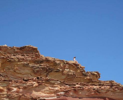 Tegan sitting atop a rock on the coastal walk
