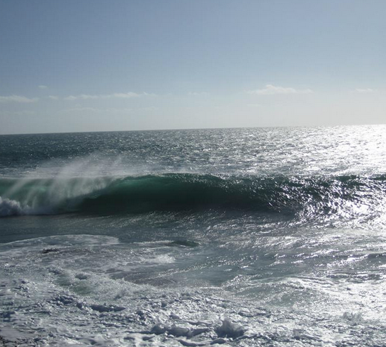 Raw energy of the ocean, big wave coming through, strong offshore wind