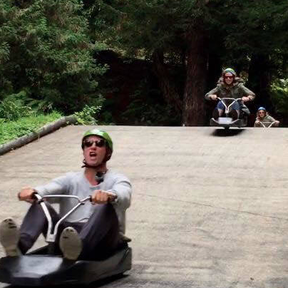 Dan flying down the road on his luge cart, Tracy coming up behind getting some air over the jump