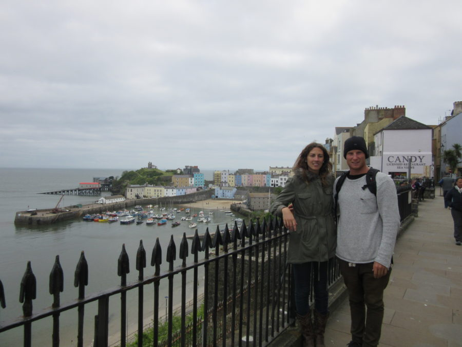 Couple shot all rugged up standing next to a black picket style fence in Tenby. Boats in the background, grey skies above.