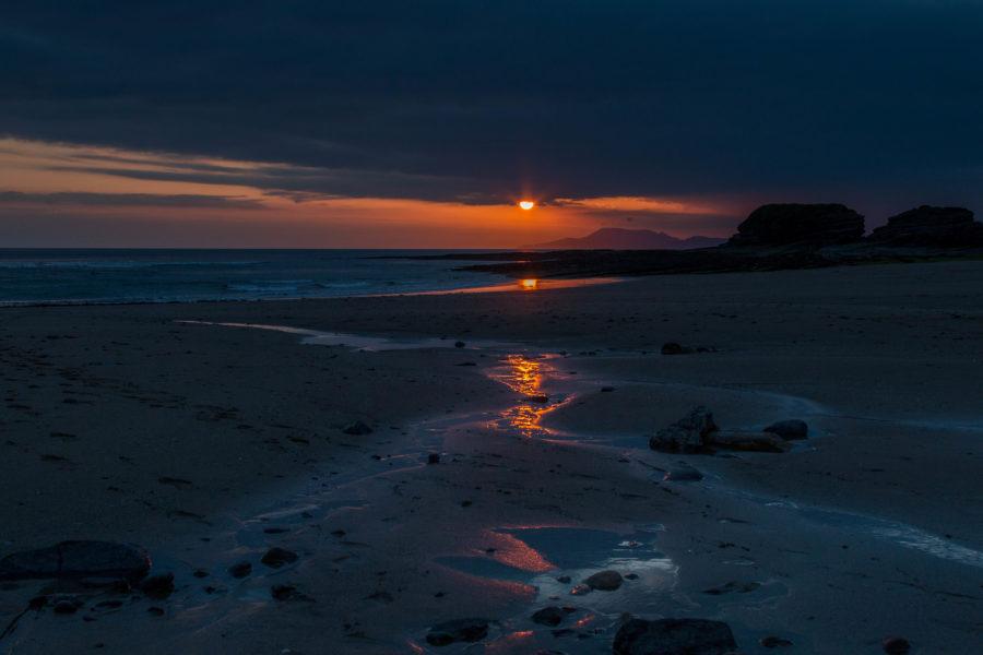 Sunset over the beach, orange ball reflecting light on the wet sandy beach