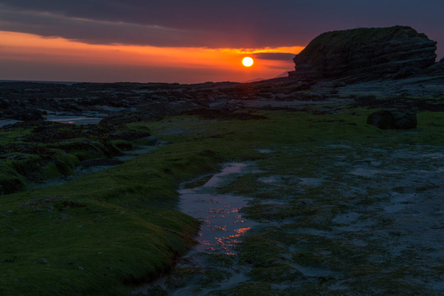 Sunset over the beach in Bundoran, vibrant green moss covering the wet rocks, a huge rocky outcrop int he distance to the right and the orange sun setting lighting the sky up