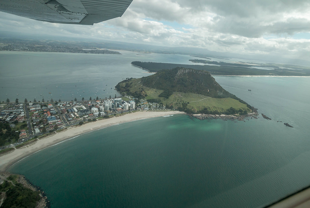 Air View of Mount Maunganui, blue ocean, big strip of white sand, green mountain, lime green on the bottom half and dark green around the top