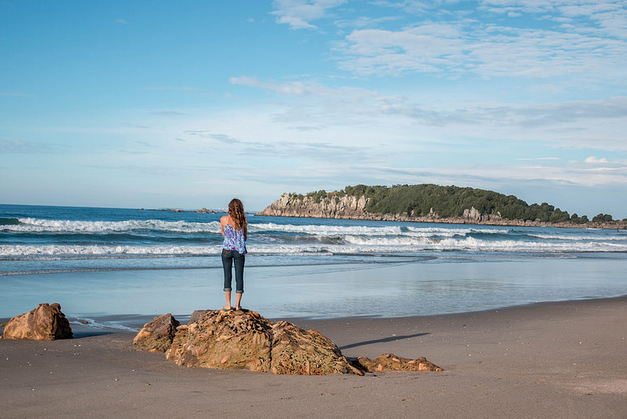 Tegan standing on a small rock on Mount Main Beach looking out over the calm sea. Blue skies and a few clouds floating around