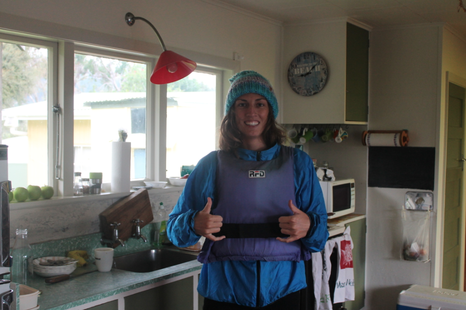 Tegan wearing a beanie, pants and jacket under a lifejacket for kayaking in the cold sea