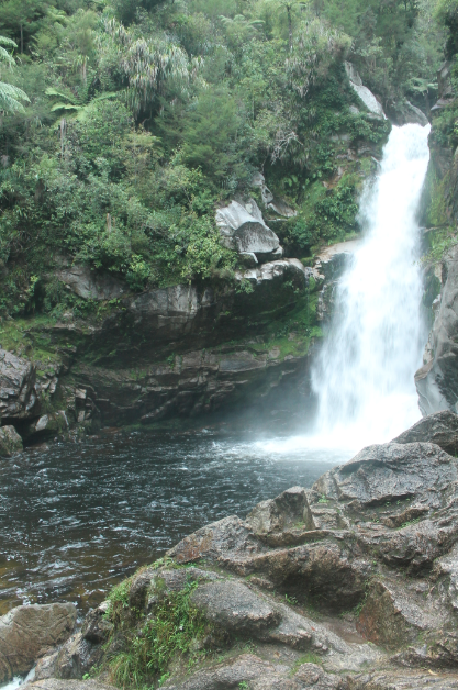 Waterfall in the Able Tasman National park, big stream of water gushing down, a bit windy creating chop on the pool below, greenery surrounding the falls