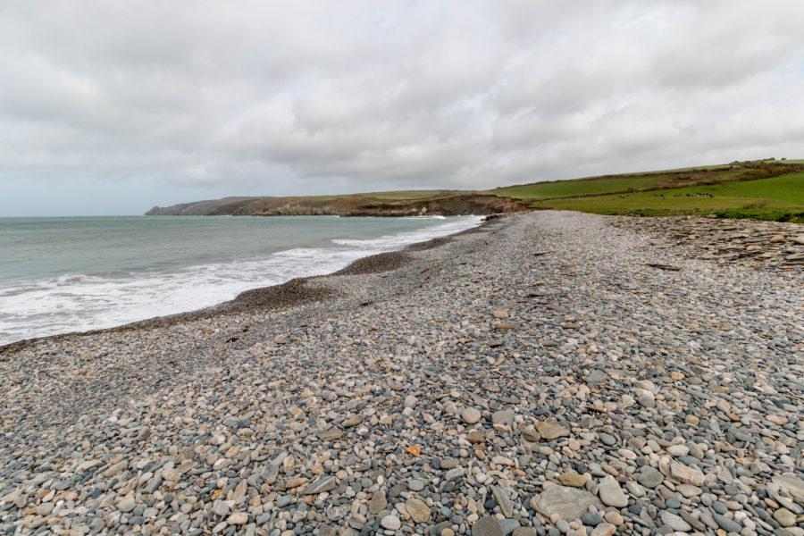 Pebble/rock beach, grey skies to match the beach and greenish water