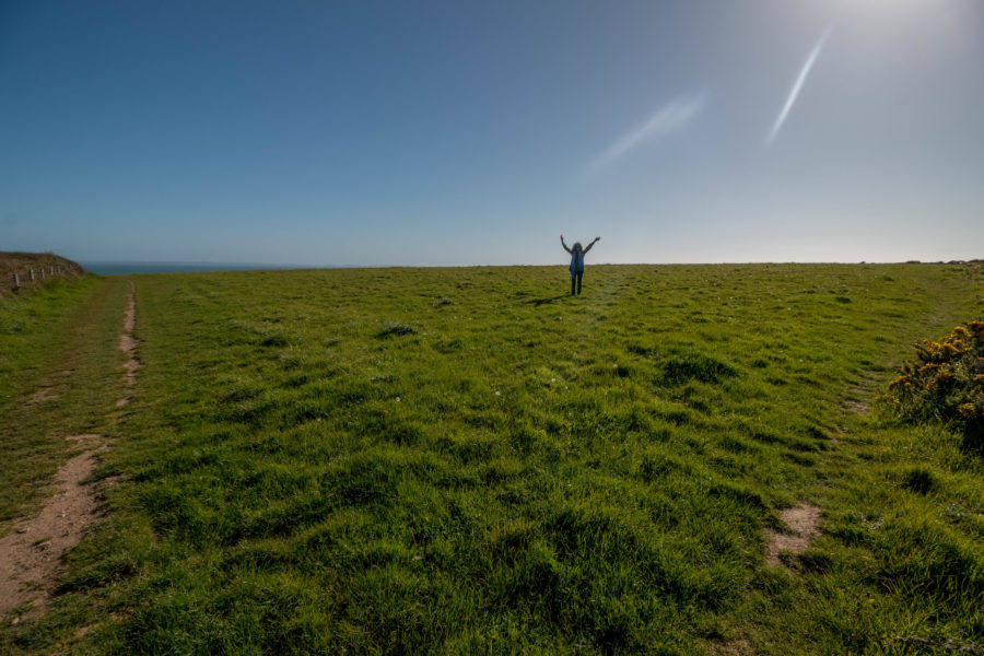 Tegan standing in a HUGE open field, vibrant green grass and blue skies