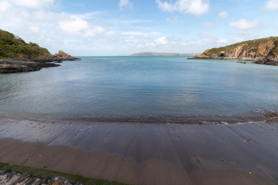 Calm blue ocean, dark brown sand, blue skies.